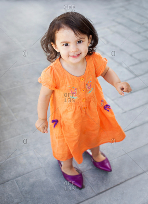 Girl wearing adult shoes and smiling, portrait