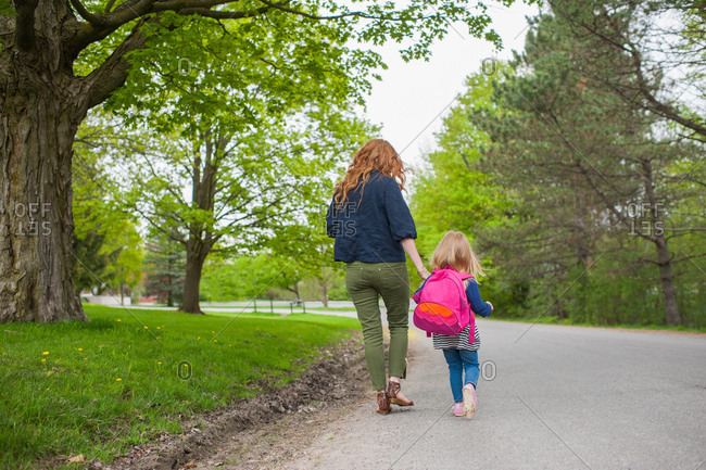 Rear view of mother and daughter holding hands walking down road through woods