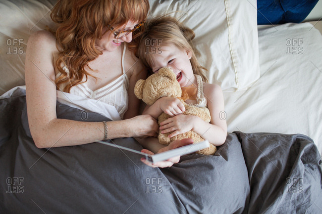 Mother and daughter lying on bed cuddling soft toy