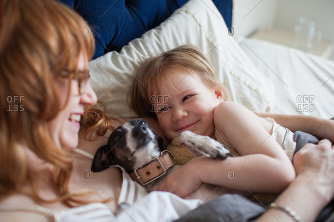 Mother, daughter and dog lying in bed