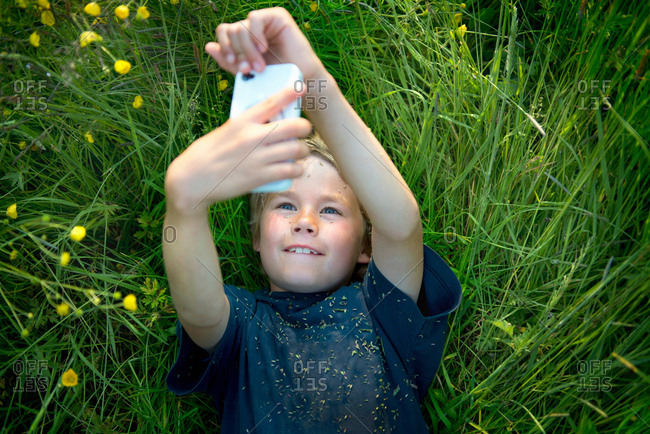 Boy lying on grass taking self portrait photograph using smartphone