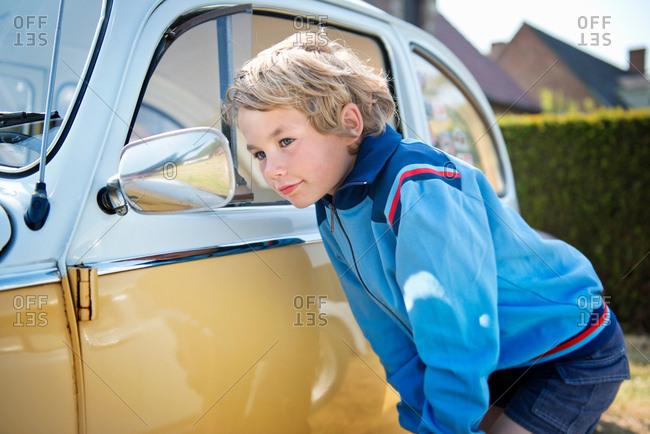 Boy looking in wing mirror of car