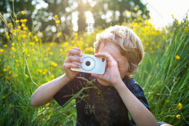Boy sitting in long grass taking photograph using smartphone