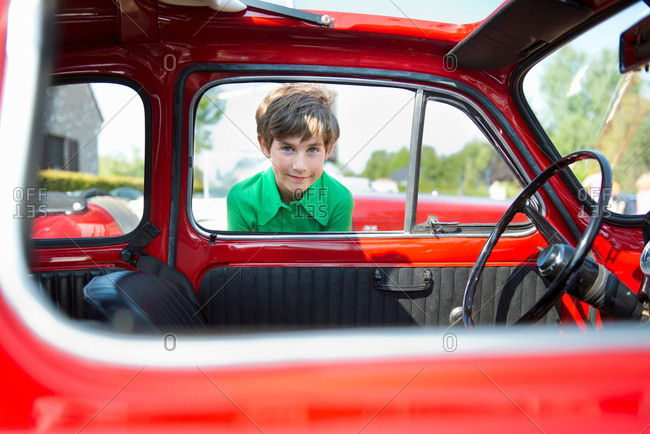 Boy looking through window of vintage automobile