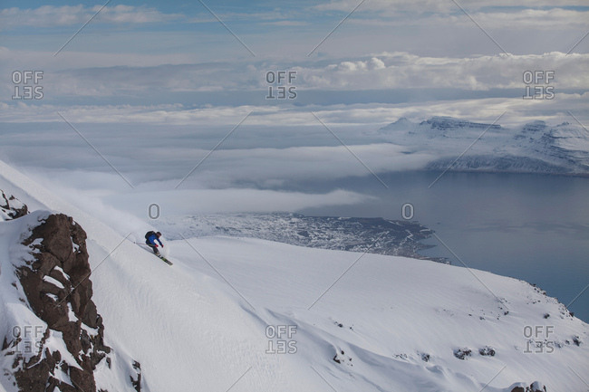 Man snowboarding down mountain at Eskifjordur, Iceland