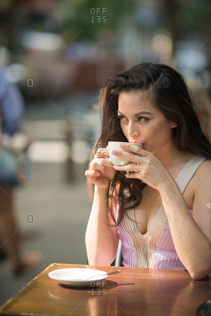 Mid adult women drinking coffee in pavement cafe