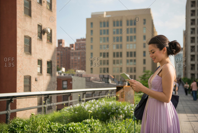 Mid adult women using digital tablet in High Line Park, New York City
