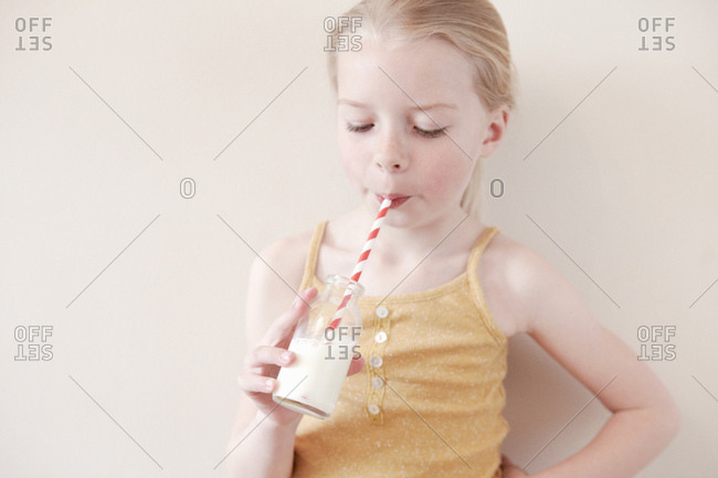 Young girl drinking glass of milk through straw