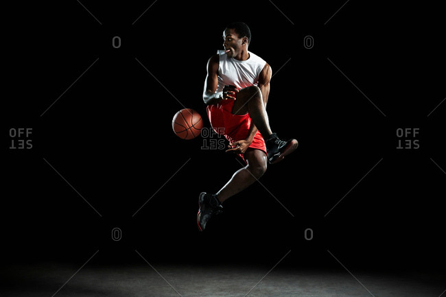 Young male basketball player mid air