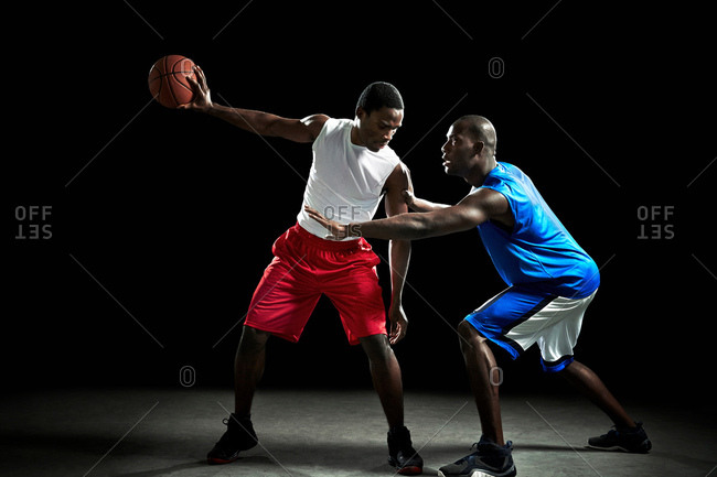 Young male basketball players competing for ball