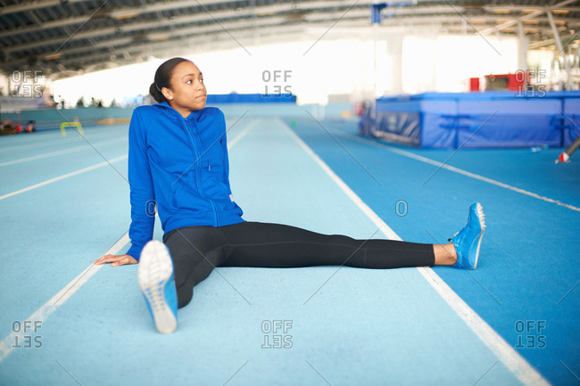 Young female athlete sitting on floor stretching legs