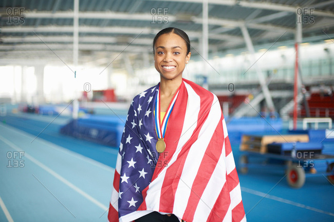Young female athlete wrapped in US flag with gold medal