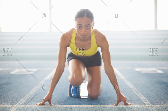 Young female athlete on starting blocks