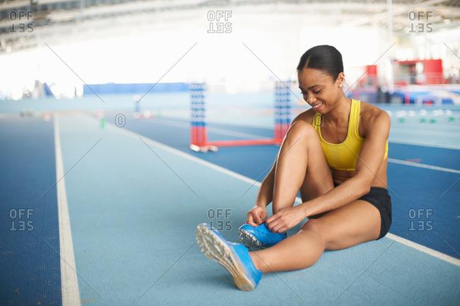 Young female athlete sitting on floor tying shoelace
