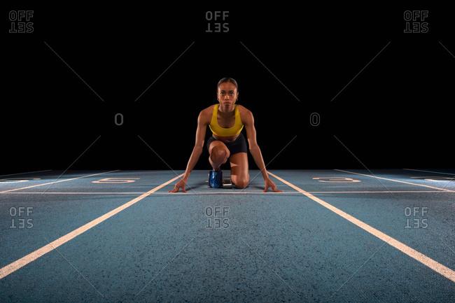 Young female athlete on starting blocks