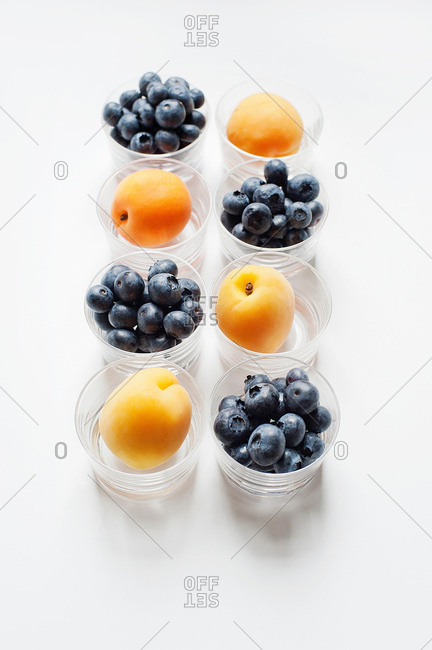 Still life with rows of apricots and blueberries in glass tumblers