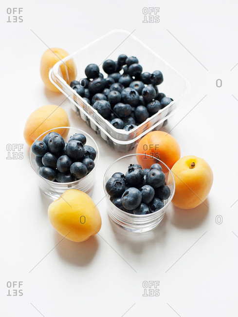 Still life with apricots and blueberries in glass tumblers