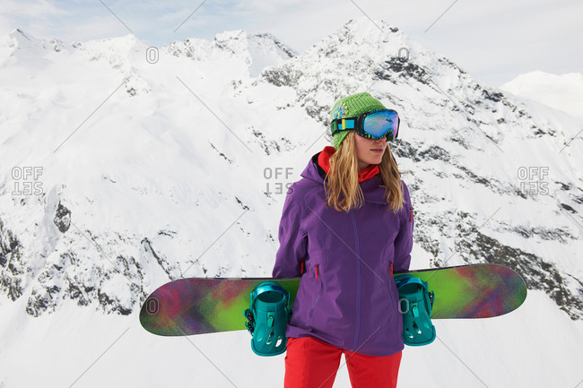 Young woman holding snowboard at top of mountain