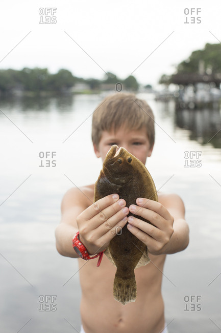 Portrait of boy holding up flounder, Shalimar, Florida, USA
