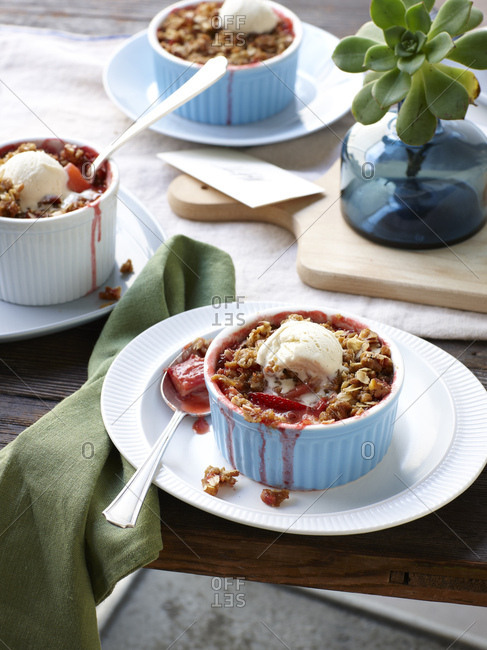 Still life of rhubarb, apple and strawberry crumble with ice cream