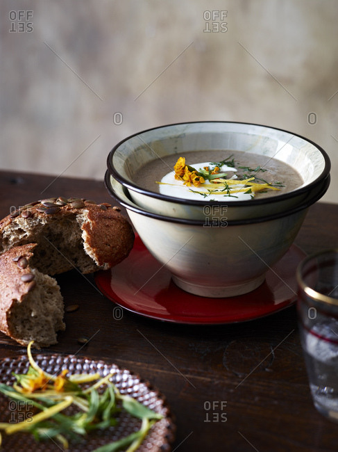 Table with bowl of mushroom and tarragon soup and brown bread