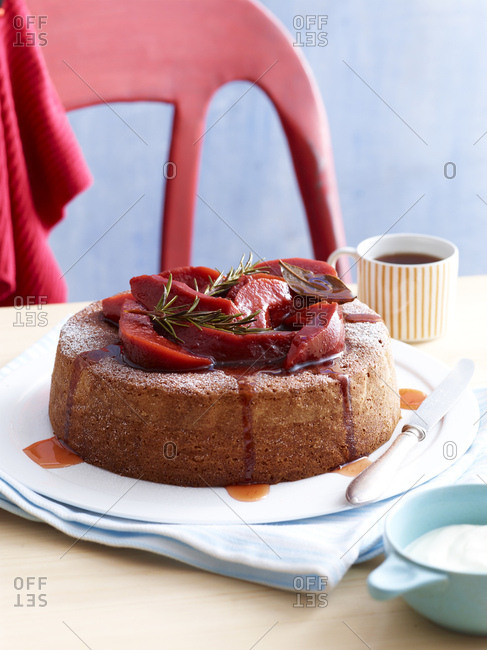 Olive oil cake with fruit and rosemary garnish