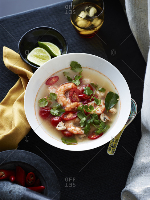 Bowl of Tom yum soup with herb garnish