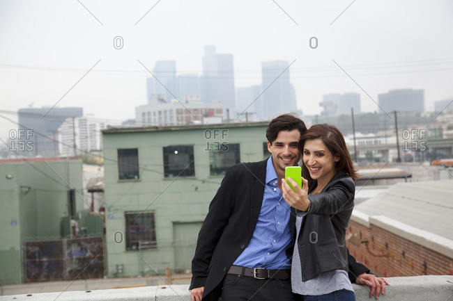 Couple making self portrait on city rooftop