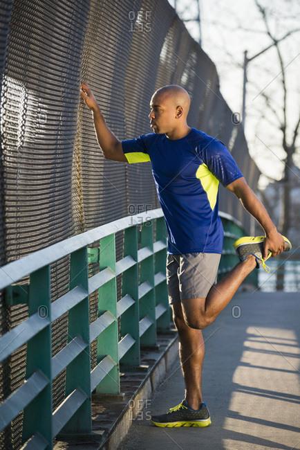 Man stretching on sidewalk