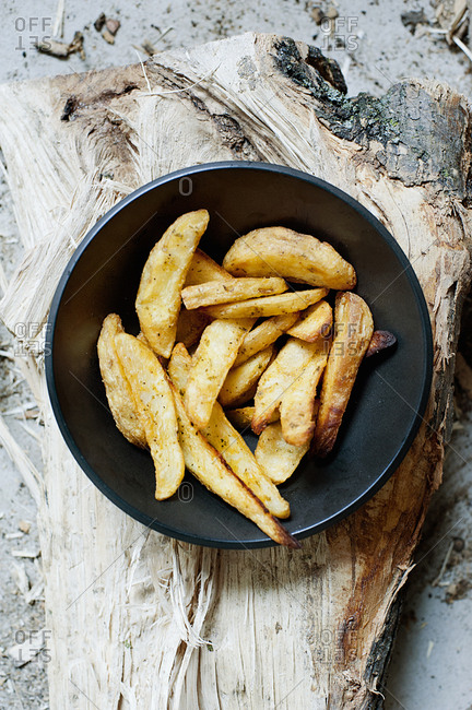 Bowl of homemade chips on wooden board