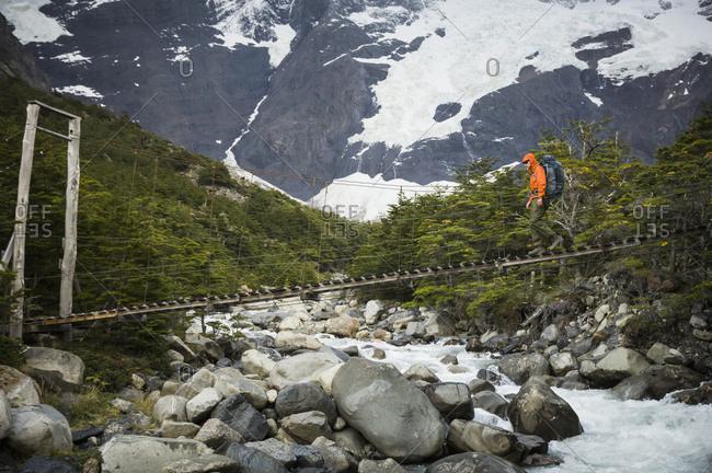 Man crossing bridge over Rio del Frances, Torres del Paine National Park, Chile