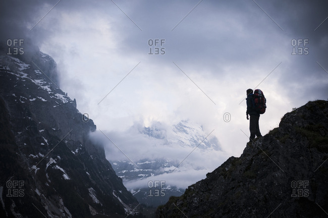 Man standing on rocks with Mount Eiger in background, Bernese Oberland, Switzerland
