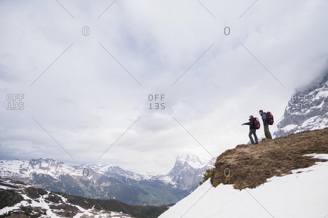 Couple hiking near Klein Scheidegg at the base of mount Eiger, Adelboden, Bernese Oberland, Switzerland