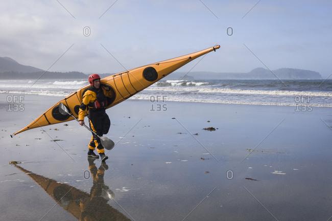 Man carrying kayak on Hobuck Beach, Makah Bay, Washington, USA