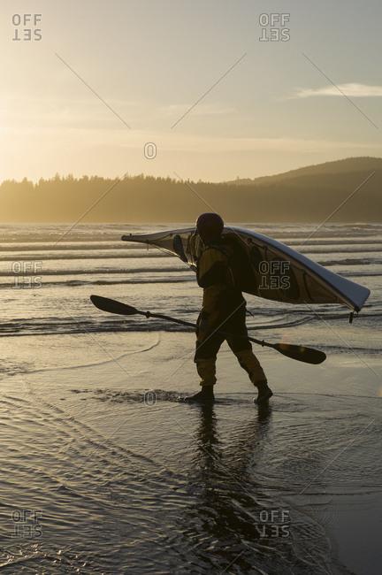 Man carrying kayak on beach at Bahobohosh Point, Makah Bay, Washington, USA