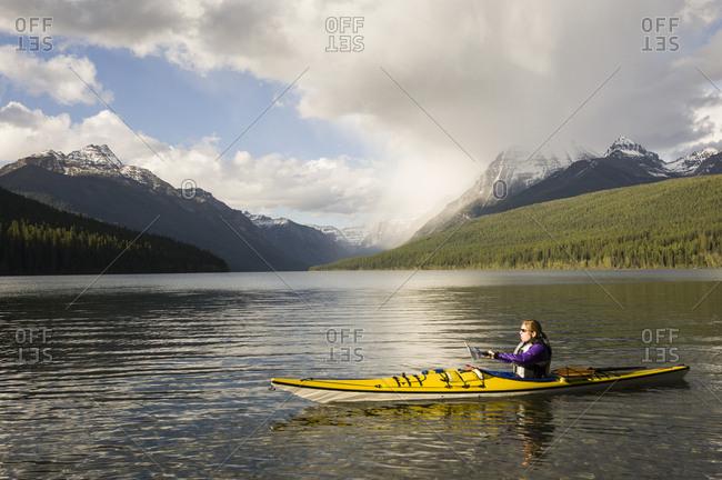 Female kayaking on St. Mary Lake, Glacier National Park, Montana, USA