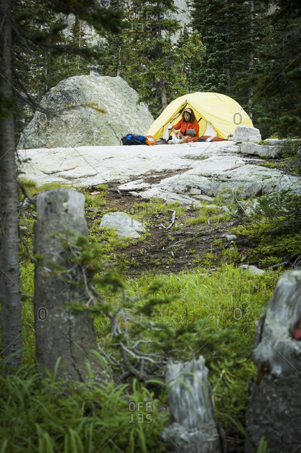 Woman camping near Crater Lake at the base of Lone Eagle Peak, Indian Peaks Wilderness, Colorado, USA