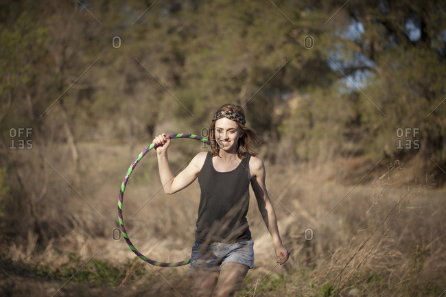Young woman carrying toy hoop in field