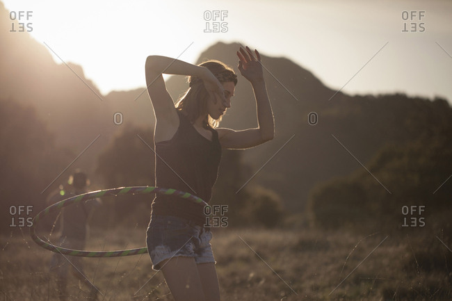 Young woman performing with toy hoop, Malibu Creek State Park, California, USA