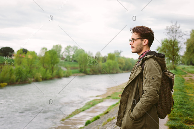 Man standing in park by river