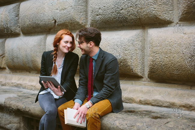 Couple sitting using digital tablet, Florence, Italy