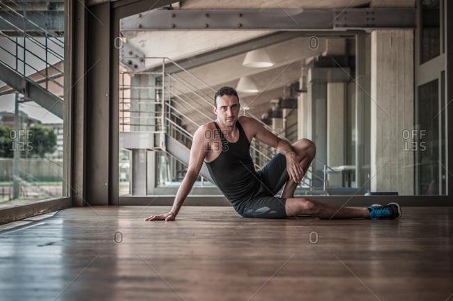 Mid adult man sitting on gym floor