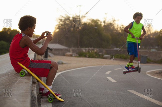 Boy photographing brother doing push scooter jump on road