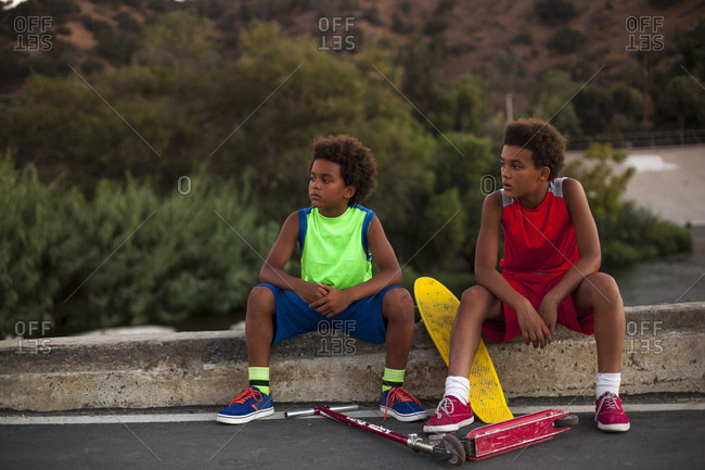 Two brothers with skateboard and push scooter watching from curb