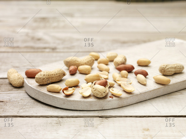 Peanuts, whole and cracked open monkey nuts on wooden chopping board