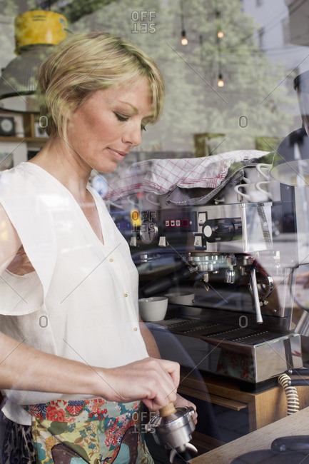 Mid adult woman making coffee in cafe
