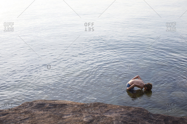 High angle view of teenage boy looking down at Lake Superior, Au Train, Michigan, USA