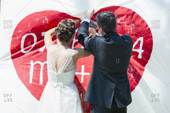 Rear view of bride and groom cutting a heart out of a banner