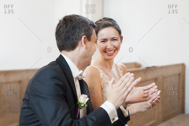 Bride and bridegroom clapping whilst sitting on church pew