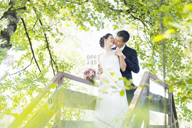 Romantic newlywed mid adult couple kissing on footbridge in park